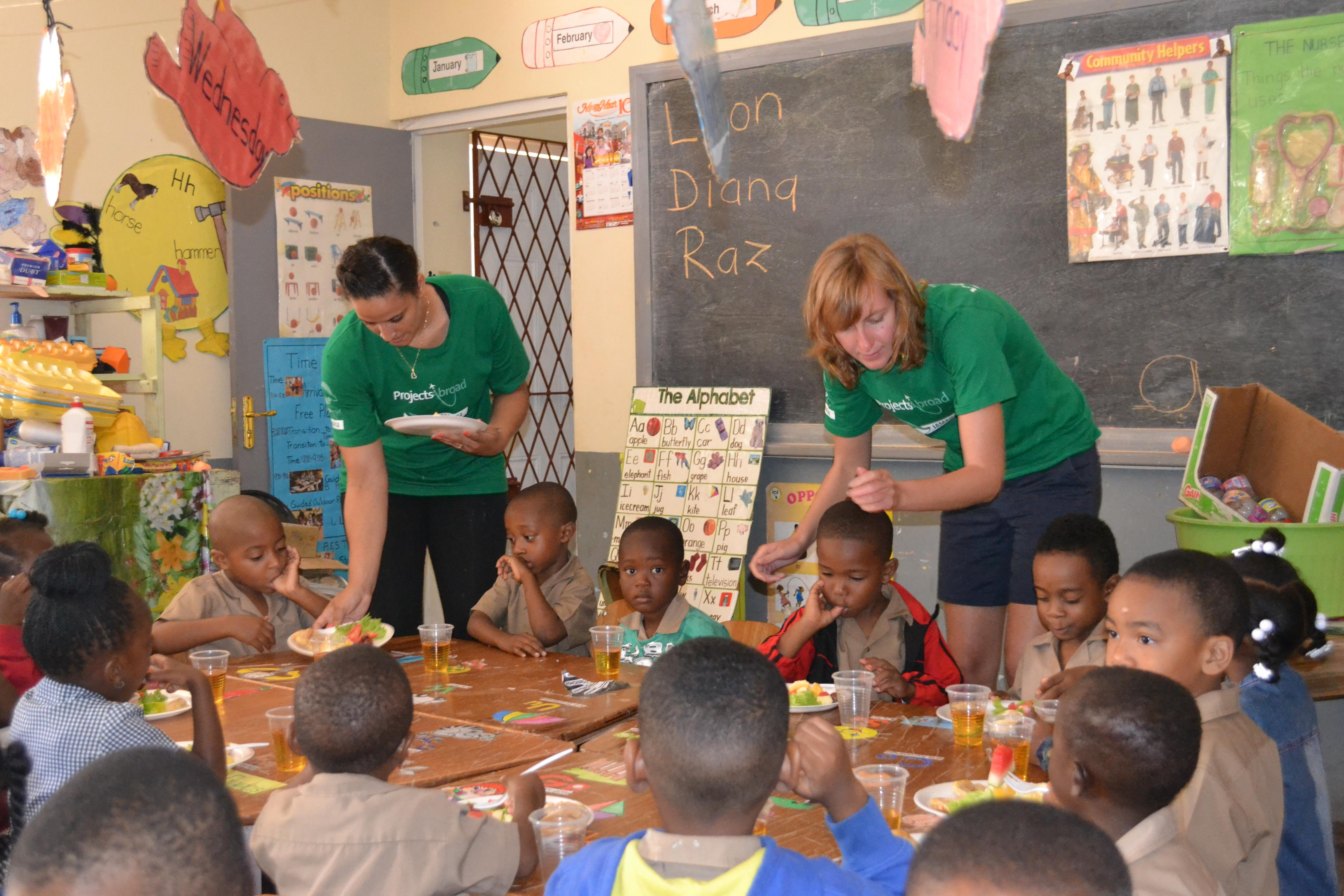 Two volunteers working with children in Jamaica serve breakfast to children at a kindergarten during a nutritional outreach.